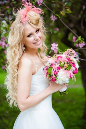 Very beautiful bride blonde curly hair in a white dress and deli