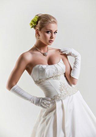 Portrait of beautiful delicate blonde bride in wedding dress wit