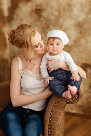 Beautiful slim blonde mom in white T-shirt holds a little girl i