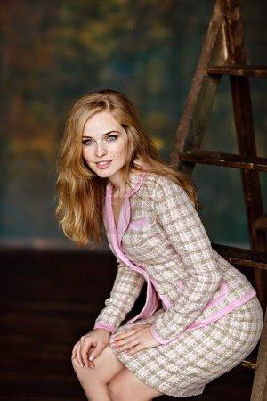 Photo pour Portrait de sensuelle très belle fille rousse avec des taches de rousseur dans un costume de tweed, assis sur les escaliers à l'intérieur - image libre de droit