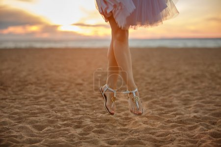 Photo of woman's feet in a lush short skirt Bouncing on the sand