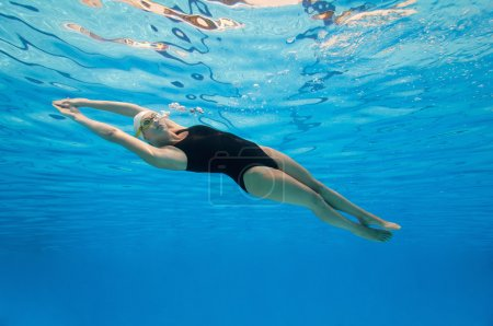 woman swimming under the water surface