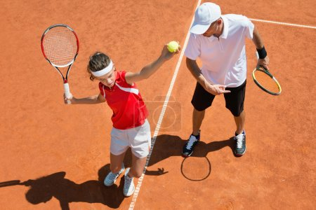 Practicing tennis service with tennis coach