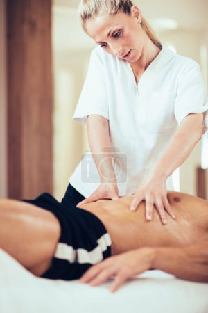 Physical therapyst massaging sportsman