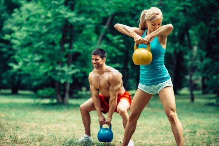 Couple working out with kettle bells