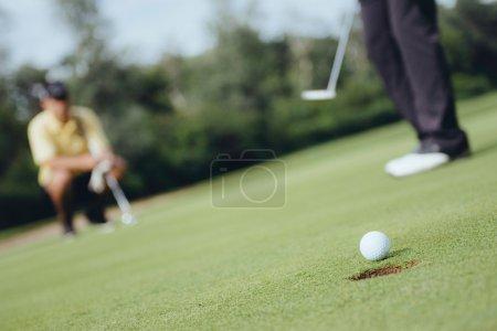 Photo pour Détail du jeu de golf. Focus sur balle, golfeurs en arrière-plan - image libre de droit