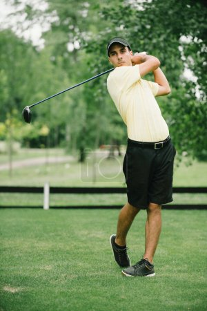 Golf swing by young man