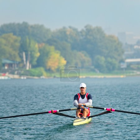 athlete rowing training on lake