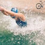 Female triathlete in training, running into water...