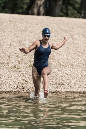 female athlete running into the water