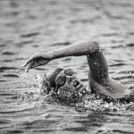 Black and white triathlon female competitor swimmi...