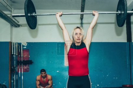 Photo for Blond Female lifting weights in sports center - Royalty Free Image