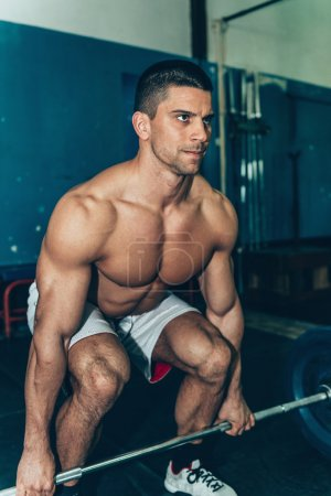 Photo for Young Strong caucasian man lifting weights in sports center - Royalty Free Image