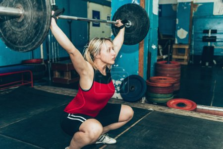 Photo for Young blond Female lifting weights in sports center - Royalty Free Image