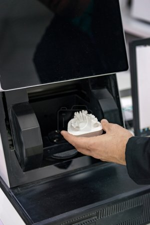Photo for Dental technician hand with denture in Dental 3d scanner in dental laoratory. - Royalty Free Image