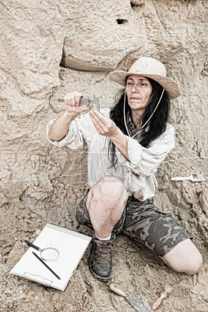 archaeologist with ancient coin