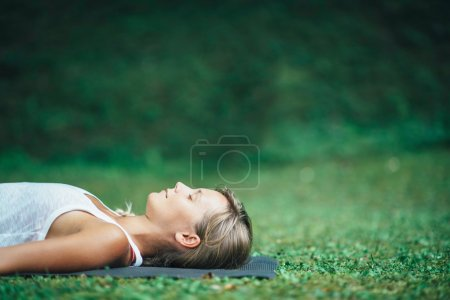 Photo for Girl meditating outdoor, Shavasana or corpse position - Royalty Free Image