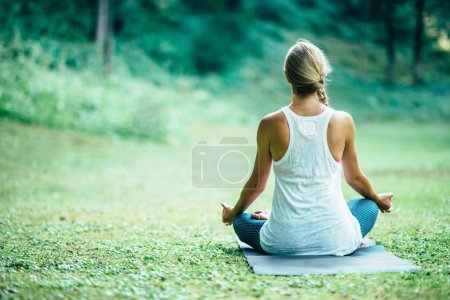 Photo for Young woman doing yoga, sitting in lotus position,  rear view - Royalty Free Image