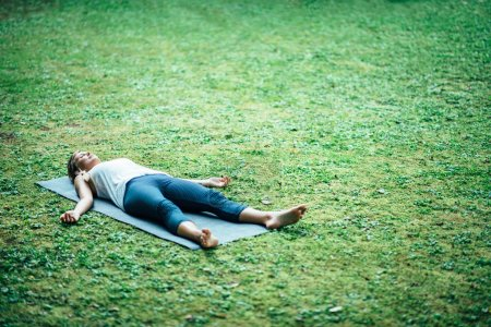 Photo for Girl meditating on grass, yoga corpse position - Royalty Free Image