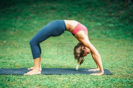 Photo pour Jeune femme faisant yoga, pose de la roue ou Urdhva Dhanurasana - image libre de droit