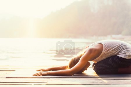 Photo for Woman practicing Yoga by the lake, Sun salutation, Balasana or child position. Toned - Royalty Free Image