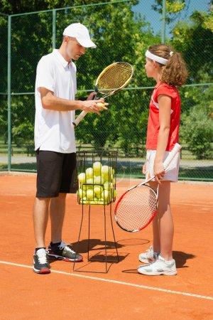 Tennis coach instructing player