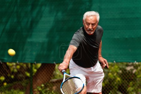 Photo for Active  Senior man in action, playing tennis - Royalty Free Image