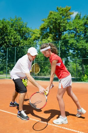 Tennis instructor working with junior player