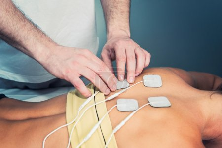 therapist positioning electrodes on patient back