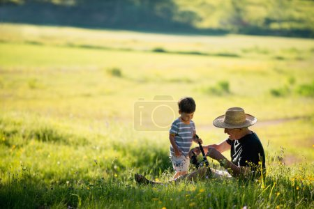 Photo for Grandfather and grandson in field outdoor activities - Royalty Free Image