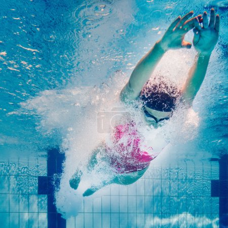 Photo for Young woman dives into swimming pool - Royalty Free Image