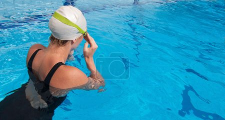 swimmer fixing goggles before starting lap