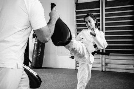 Photo for Taekwondo instructor working with little girl  during martial arts training - Royalty Free Image