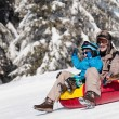 Mother and little son snow tubing down the hill on...