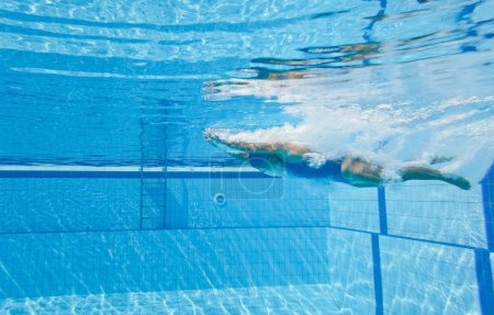 woman dives into swimming pool