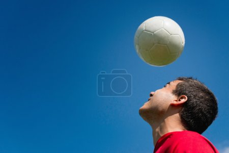 Soccer player with ball over head