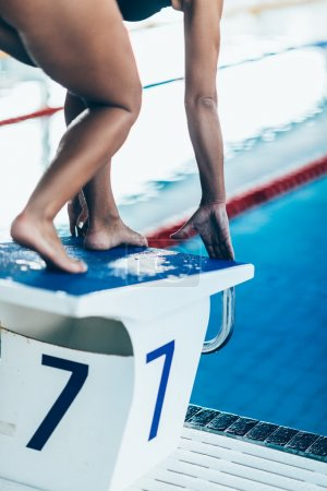 Photo for Female swimmer on start position waiting for race to start. - Royalty Free Image