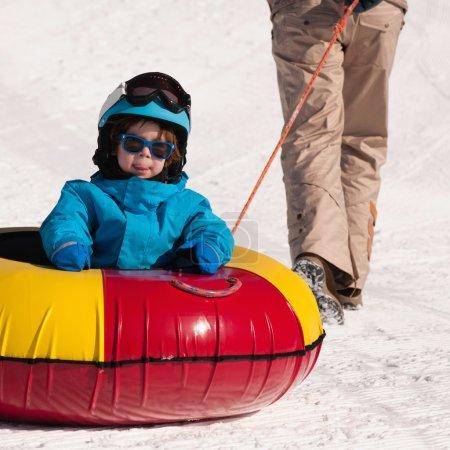 boy enjoying ride in snow tube