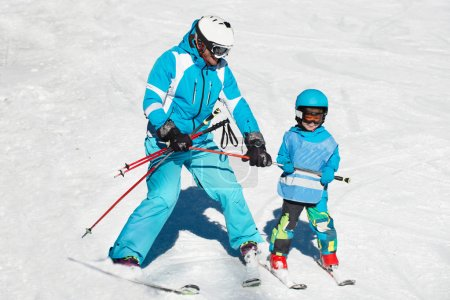 little boy skiing with instructor