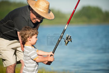 Cute little grandson fishing with his grandfather ...