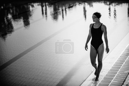 Photo pour Image en noir et blanc d'une nageuse attrayante marchant au bord de la piscine - image libre de droit