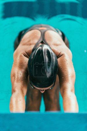 Female swimmer starting race
