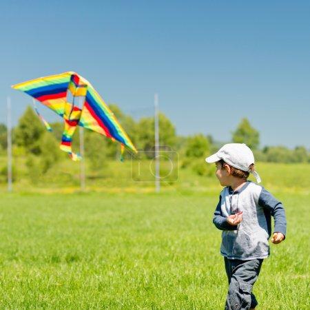Photo pour Petit garçon marche avec cerf-volant à champ vert pendant la journée - image libre de droit