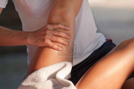 massage therapist working on athlete leg