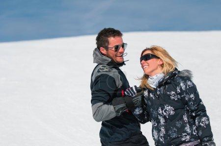 ski couple holding hands