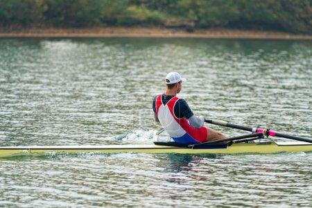 sportsman rowing single scull on lake