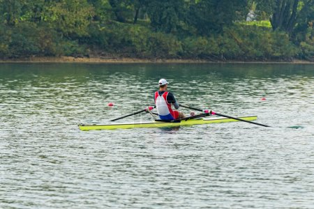 male athlete rowing single scull