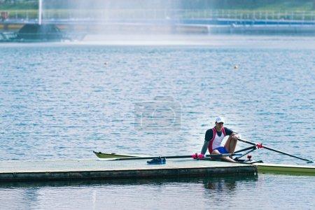 Sportsman having break after rowing