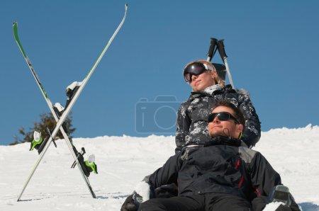 couple sunbathing on snow