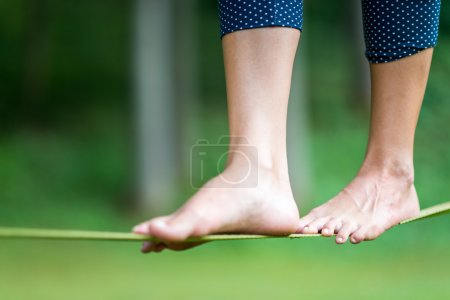 Photo for Cropped image of female legs balancing barefoot on a Slackline - Royalty Free Image